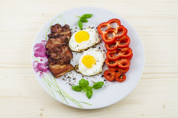 Plate with fried eggs, bacon and paprika on wooden table