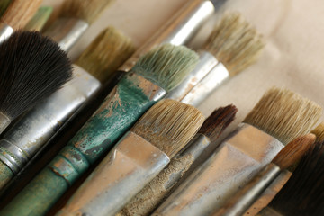 Different paintbrushes on fabric background