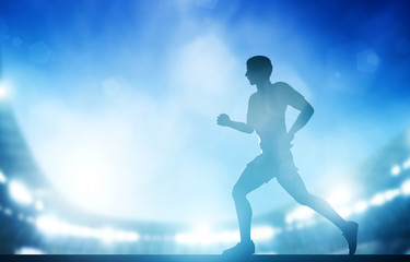 Man running on the stadium in night lights. Athletics run