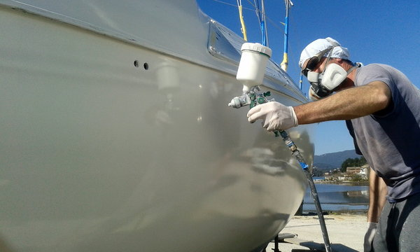 man with face mask spray painting sail boat yacht with air gun