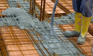 worker compacting cement in reinforcement form work