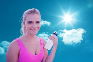 Composite image of smiling healthy woman with water bottle