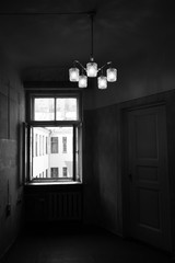 Interior of a dark emty room with switched chandelier and open window