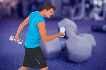 Composite image of fit man lifting heavy dumbbells