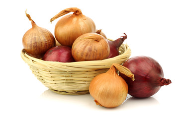 red and brown onions in a wicker basket on a white background