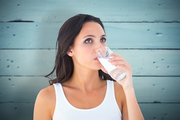 Composite image of pretty brunette drinking glass of water