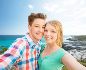 smiling couple with smartphone on summer beach