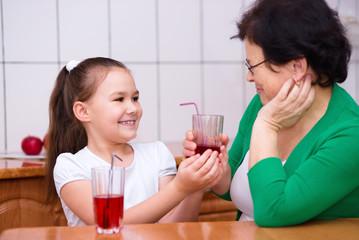 Grandmother with her grandchildren drink juice
