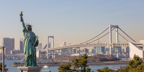 Lady liberty juxtaposed against Rainbow Bridge in Tokyo, Japan.