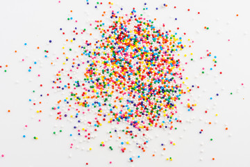 Wall Mural - Colorful round sprinkles spilled on white background, isolated