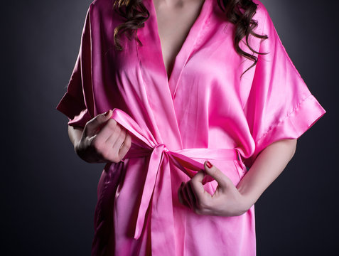 Girl tying belt of her silk robe, close-up