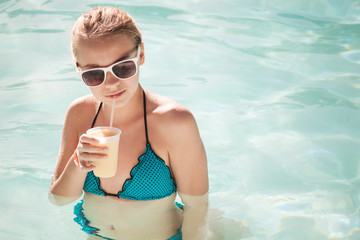 Little blond girl drinks cocktail in swimming pool