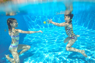 Children swim in pool underwater, girls swimming