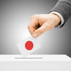 Voting concept - Male inserting flag into ballot box - Japan