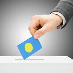 Voting concept - Male inserting flag into ballot box - Palau