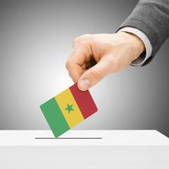 Voting concept - Male inserting flag into ballot box - Senegal