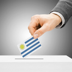 Voting concept - Male inserting flag into ballot box - Uruguay