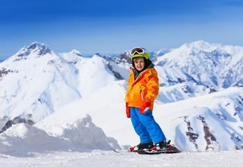 Smiling cute boy wearing ski mask, helmet skiing