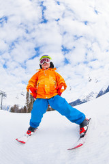 View from below of boy wearing ski mask and skiing