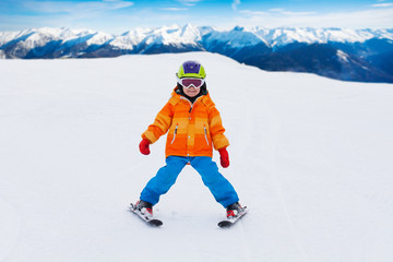 Boy wearing ski mask and helmet skiing on slope