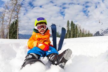 Sitting on snow boy in ski mask and helmet