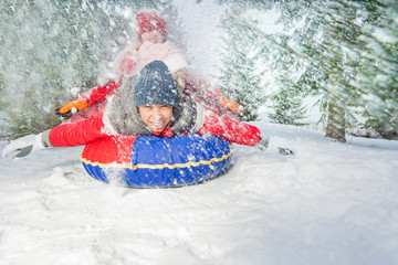 Happy friends on snow tube in winter during day