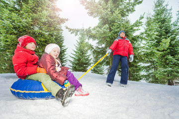 Happy kids sit on snow tube and other pulling them