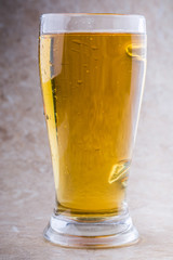full glass of beer on stone background