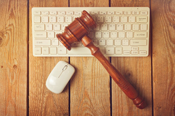 Judge gavel and computer keyboard on wooden vintage background