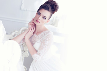 Young gorgeous bride sitting in antique interior