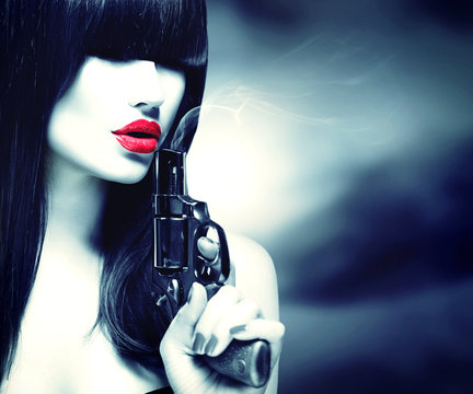 Sexy model woman with a gun. Black and white portrait