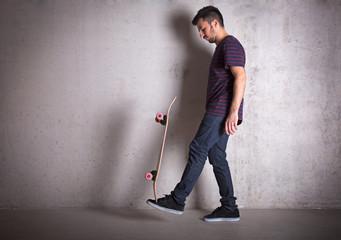 Skateboarder doing a skateboard trick, against concrete wall.