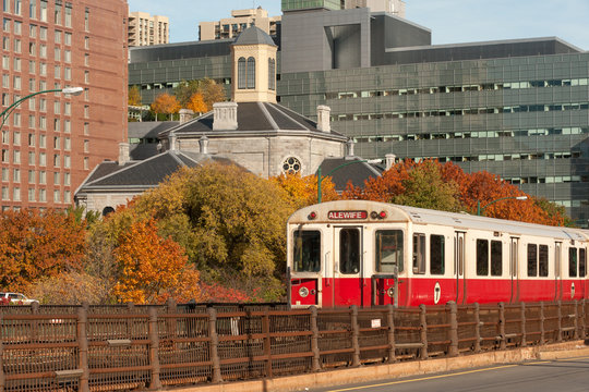 Red line subway train with Boston on background