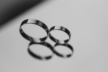 Two wedding rings laying on a mirror. black and white photo