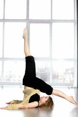 Sporty female standing in yoga Shoulderstand pose in class