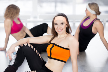 Beautiful girl resting with bottle of water in fitness class
