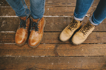 Legs of couple in boots on the wooden floor outdoors