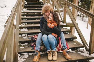 Young couple sitting on wooden stairs outdoors in winter