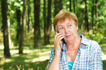 Old woman talking on the phone in the forest