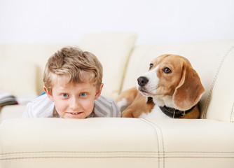 Boy and dog lying on sofa together