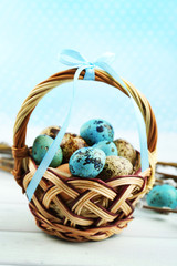 Bird eggs in wicker basket on bright background