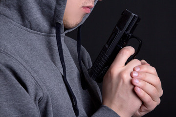 close up of gun in male hands over grey