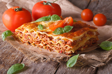 Italian lasagna with basil close-up on paper, horizontal rustic