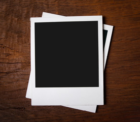 Blank instant photos on wooden background