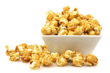 pieces of caramel  popcorn in a  bowl on a white background