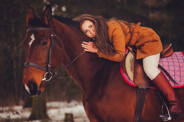 beautiful girl with long hair sitting on a horse