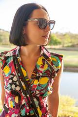 Young woman in sunglasses enjoying summer breeze at beach.