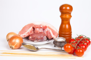 Raw meat, salt, pepper, tomatos, onion, spoon with herbs, sticks
