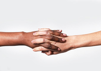Caucasian hand and black African holding fingers world diversity