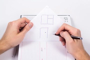 Male hand draw a house on a piece of diary